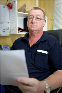 Australian Public Service employee Kevin Smith examines a document while working in his office at Camp Baird in the Middle East. Kevin is the Deputy Service Delivery Manager for maintenance and infrastructure.