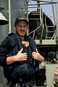 As part of HMAS Newcastle's boarding party, Able Seaman Marine Technician Tim Callus stands by to be called up as the ship and crew conduct Approach and Assist Visits while participating in Maritime Security Operations in the Middle East region.
