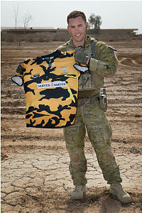 Australian Army trainer Sergeant Gus O'Neill holds a jersey from his old rugby union club, the Tamworth Pirates, at the Taji Miliary Complex, Iraq.