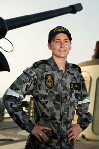 Royal Australian Navy sailor Leading Seaman Electronic Technician Ci-Anna Smith stands before HMAS Melbourne's 76mm Naval Gun. The ship is patrolling in the Middle East region for Operation Manitou.