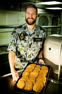 Royal Australian Navy sailor Petty Officer Marine Logistics - Cook Rob Bateman, of HMAS Darwin, presents treats for the crew as they prepare for a patrol in the Middle East region from the Naval Support Activity base in Manama, Bahrain, during Operation Manitou.