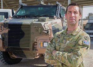 Australian soldier Private Adam Hall stands in a secure compound with a Bushmaster Protected Mobility Vehicle at the main Australian logistic base in the Middle East.