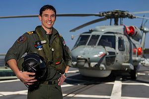 Helicopter pilot Lieutenant Caleb Muggeridge stands on the flight deck before HMAS Arunta's S-70B Seahawk while on patrol in the Middle East Region.