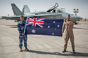 oyal Australian Air Force Ground Liaison Officer Flight Lieutenant Daniel Gusthart (left) and a pilot from the Air Task Group, hold an Australian National Flag prior to it being flown in the cockpit of an Operation OKRA mission out of the main air operating base in the Middle East.