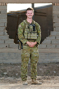 Australian Army officer Captain Matthew Fensom, deployed with Task Group Taji 4, stands near a dilapidated building at the Taji Military Complex in Iraq.