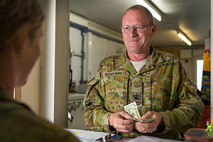 Australian Army Warrant Officer Class Two Cameron Buchanan provides cash to a member of Task Group Afghanistan at Hamid Karzai International Airport in Kabul, Afghanistan.