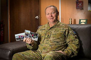 Australian Army Lieutenant Colonel Stuart Graham holds photos of his family at Australia's main operating base in the Middle East region.