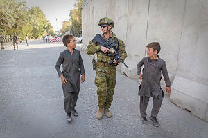 Australian Army soldier Lance Corporal Hayden Heath talks to two Afghan children during a foot move to the Afghanistan Ministry of Defence in Kabul, Afghanistan.