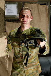 Australian Army storeman Private Hugh McNeil holds a combat helmet at a warehouse on Australia's main base in the Middle East