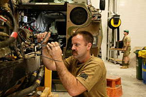 Australian Army vehicle mechanic Craftsman Gareth Turner works on a Bushmaster Protected Mobility Vehicle at Australia's main base in the Middle East.