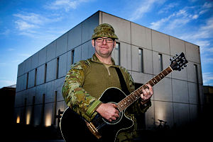 Australian Army soldier Corporal Kenn Melksham of the Theatre Communications Group sings and plays guitar during a rehearsal at the Hamid Karzai International Airport Rally Point Chapel in Kabul during his deployment to Afghanistan on Operation Highroad.