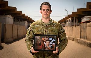 Australian Army officer, Captain Evan Smith, with a photo of his son, at Taji Military Complex, Iraq.