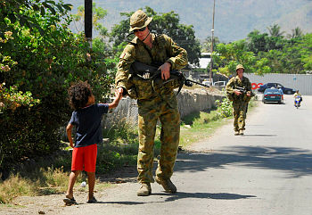 A rifleman with Battle Group Timor-Leste 3 greets a young local during a routine patrol around Dili.
