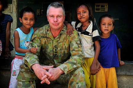 Joint Task Force 631 Padre, Captain Stephen Bennett, interacts with locals on a walk outside of Forward Operating Base Phoenix, Dili, Timor-Leste.