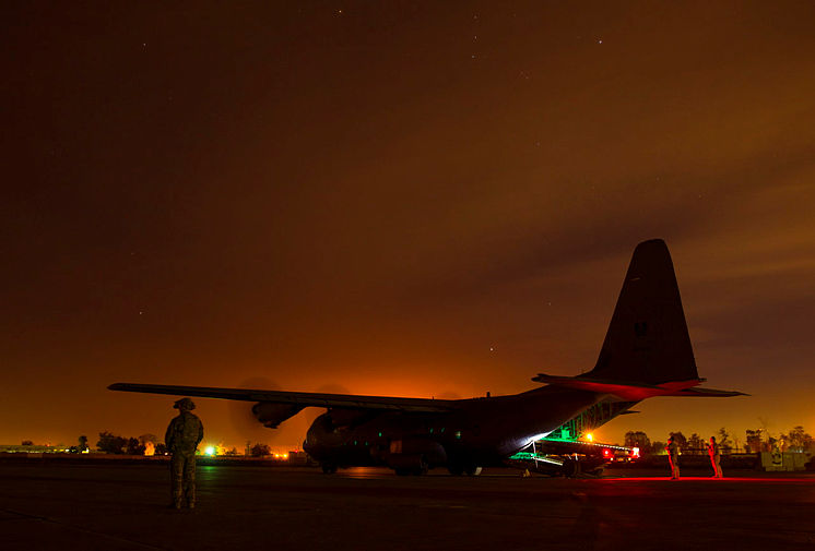 A Truck Aircraft Loading Unloading (TALU) vehicle is unloaded from a Royal Australian Air Force C-130J Hercules at the Taji Military Complex, Iraq.